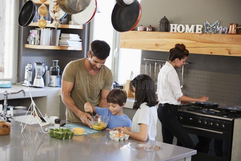 Familia en la cocina que hace el desayuno de la mañana junto imagen de archivo libre de regalías