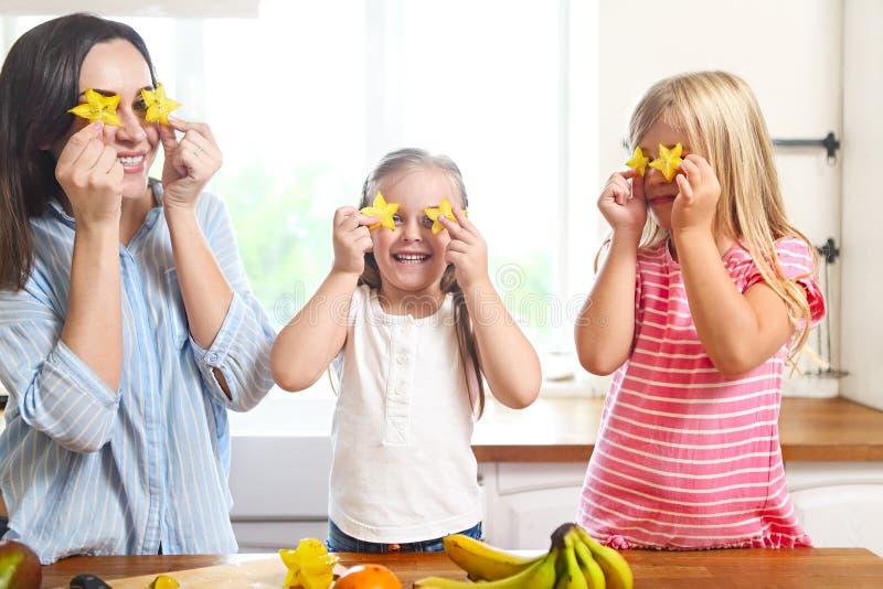 Familia en la cocina que prepara una ensalada de fruta fresca en el kitch foto de archivo