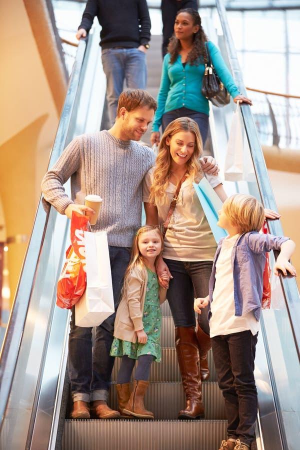 Familia en la escalera móvil en alameda de compras junto imagen de archivo