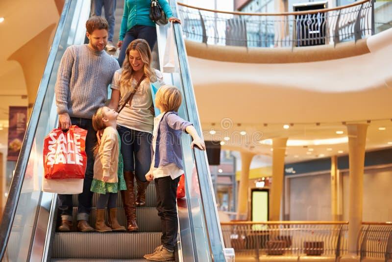 Familia en la escalera móvil en alameda de compras junto imagenes de archivo