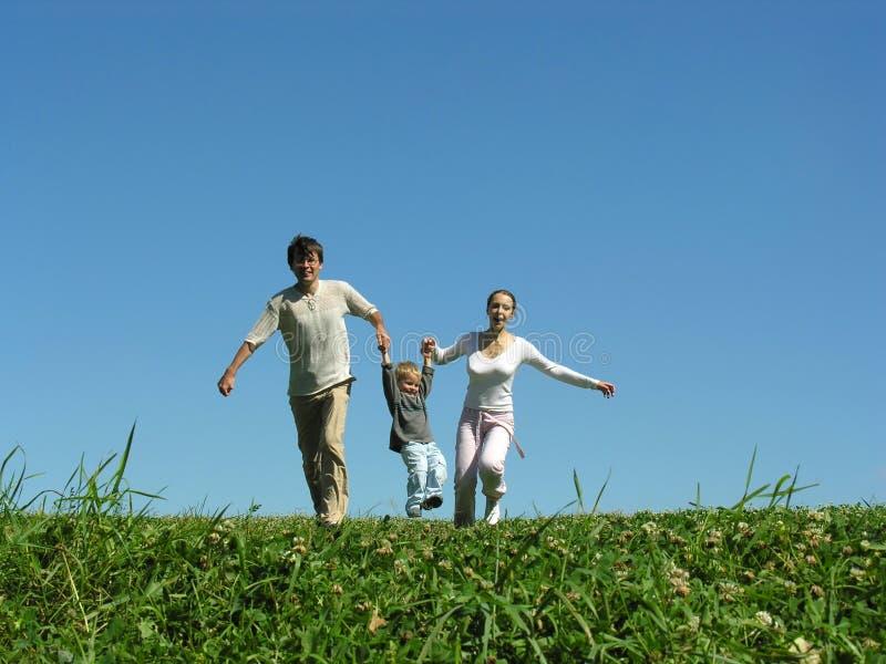 Familia en la hierba bajo el cielo azul imagenes de archivo