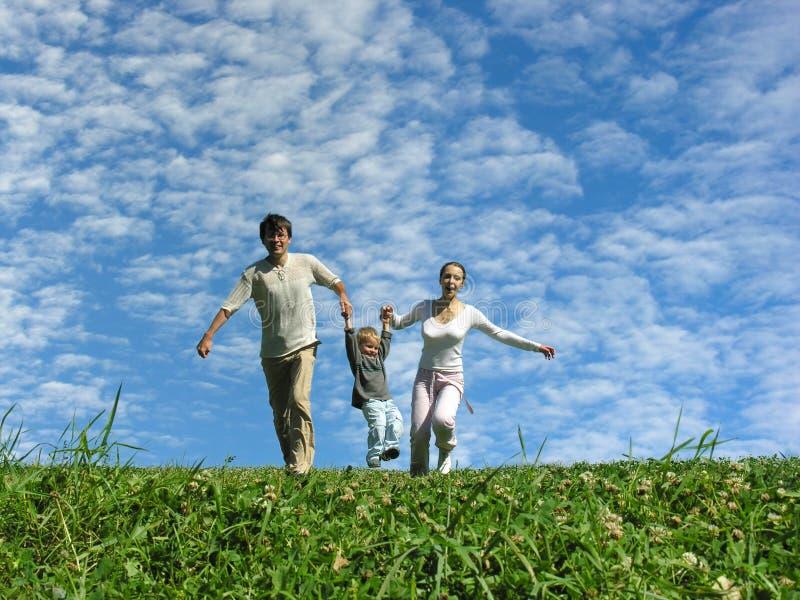 Familia en la hierba bajo el cielo azul foto de archivo libre de regalías