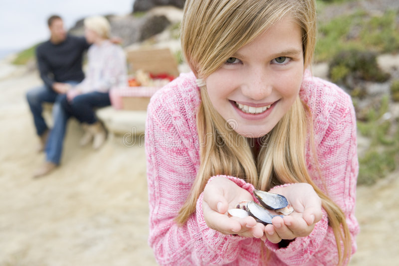 Familia en la playa con comida campestre y la muchacha con el shell foto de archivo libre de regalías