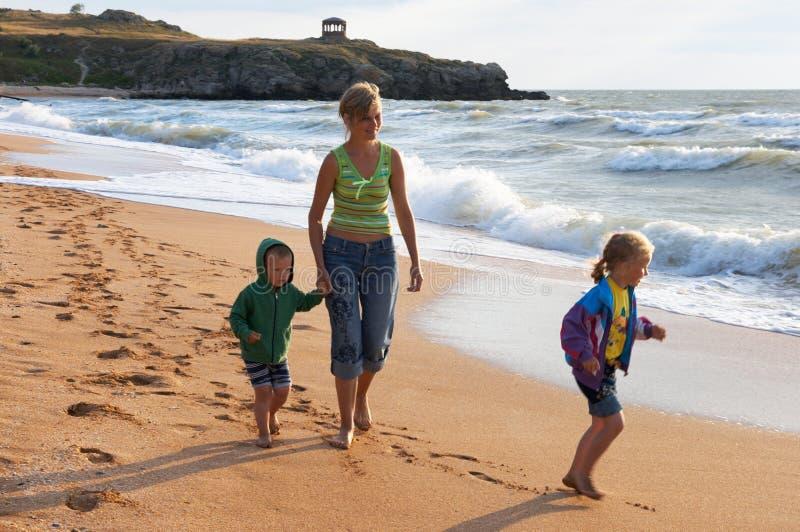 Familia en la playa de la resaca foto de archivo