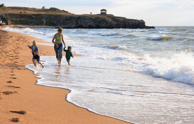 Familia en la playa de la resaca fotos de archivo