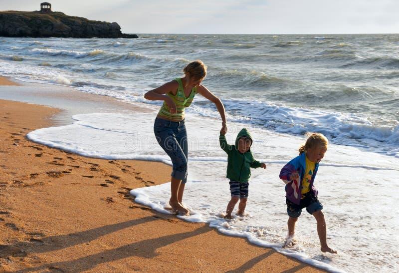 Familia en la playa de la resaca imagen de archivo libre de regalías