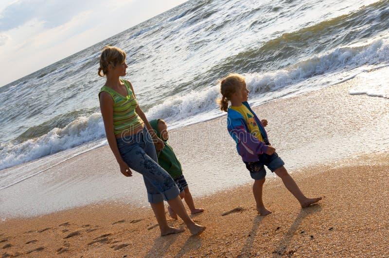 Familia en la playa de la resaca imagenes de archivo