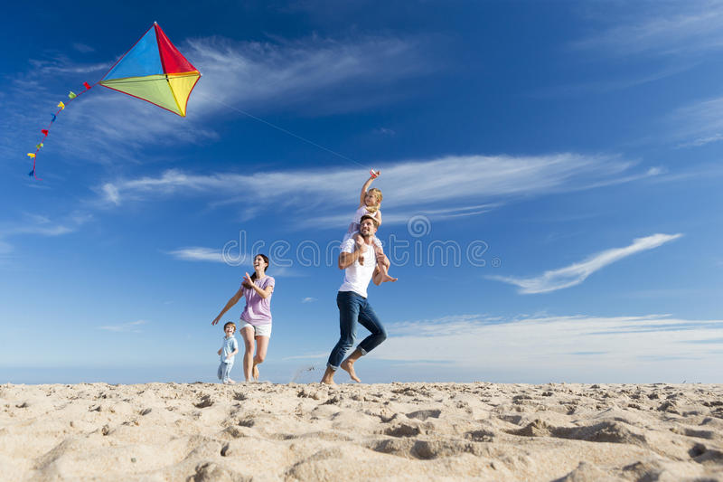 Familia en la playa Flting una cometa imagen de archivo libre de regalías