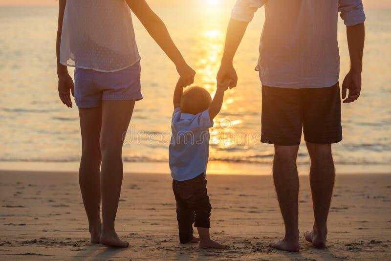 Familia en la playa, madre que celebra la mano de su hijo y caminar, fotos de archivo