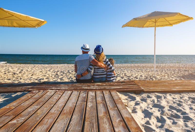 familia en la ropa rayada que se sienta en la playa imágenes de archivo libres de regalías