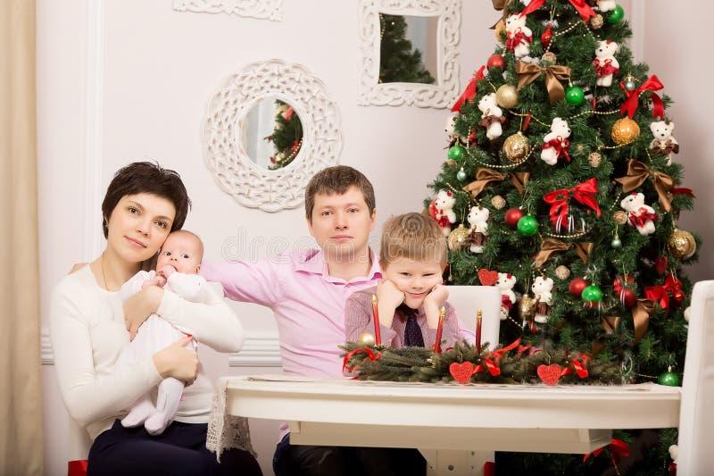 Familia en la tabla del día de fiesta Árbol Año Nuevo fotografía de archivo
