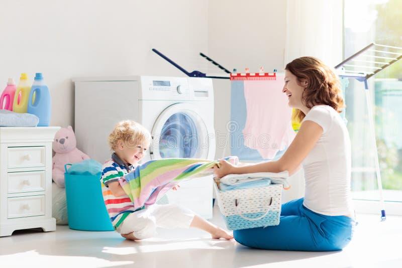 Familia en lavadero con la lavadora fotografía de archivo libre de regalías