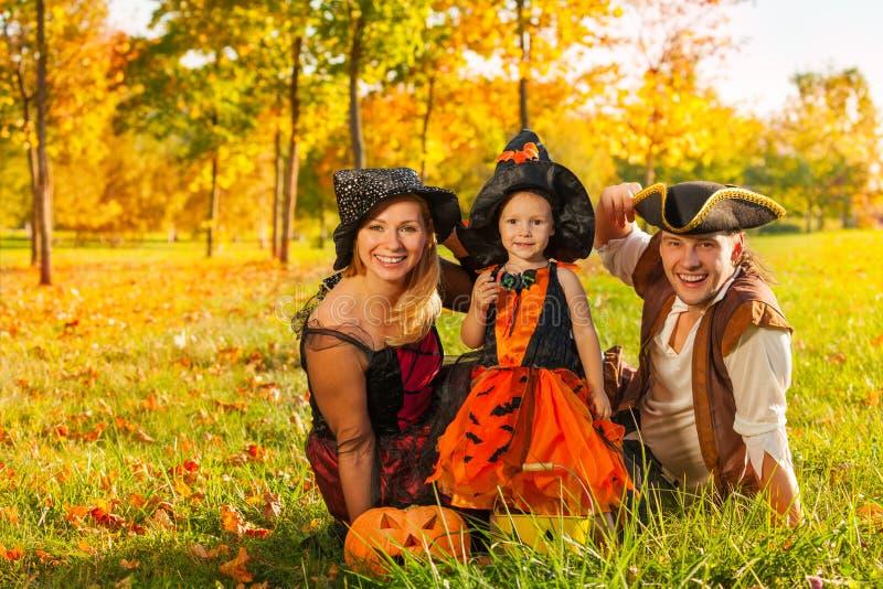 Familia en los disfraces de Halloween que se sientan en la hierba fotos de archivo libres de regalías