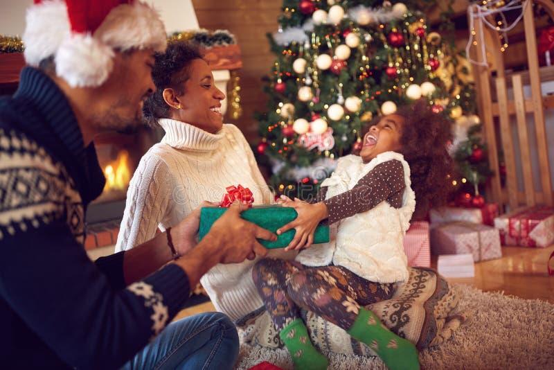 Familia en los regalos de la abertura de la Navidad que se sientan en piso en casa fotografía de archivo libre de regalías