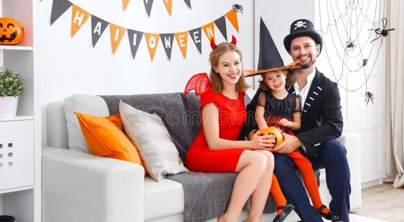 familia en los trajes que consiguen listos para Halloween en casa imagen de archivo