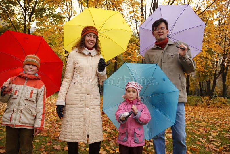 Familia en parque del otoño con los paraguas coloreados imagen de archivo libre de regalías