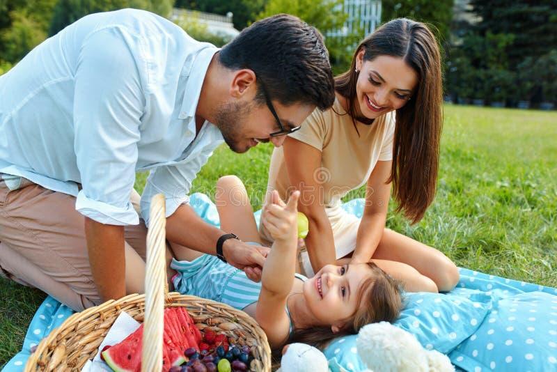 Familia en parque Padres felices y niño jovenes que se relajan al aire libre fotografía de archivo