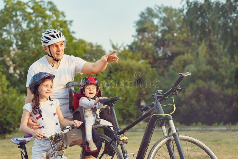Familia en paseo del ciclo en campo imagen de archivo