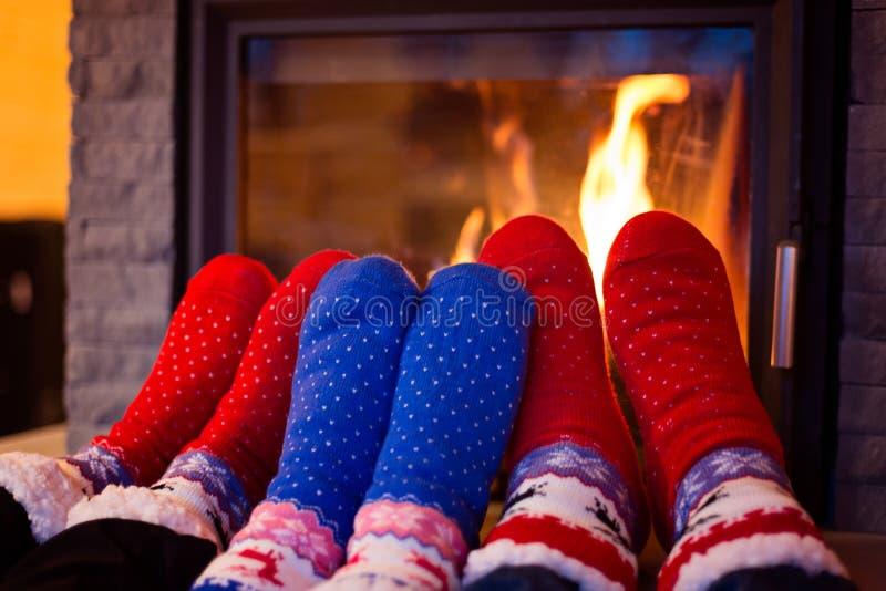 Familia en pies que se calientan del calcetín de lana fotografía de archivo