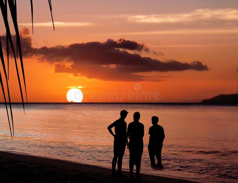 Familia en puesta del sol del paraíso. imagenes de archivo