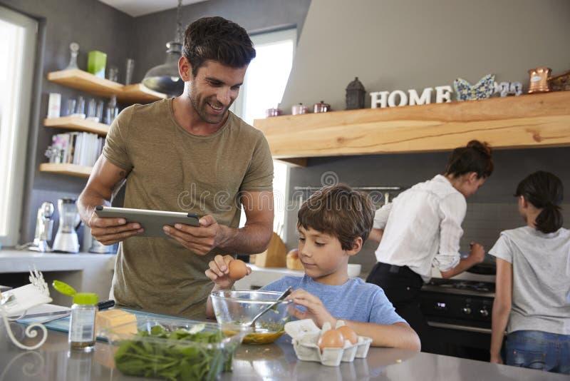 Familia en receta de siguiente de la cocina en la tableta de Digitaces junto foto de archivo libre de regalías