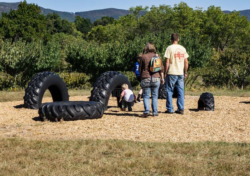 Familia en un área de juego grande del neumático imagen de archivo libre de regalías