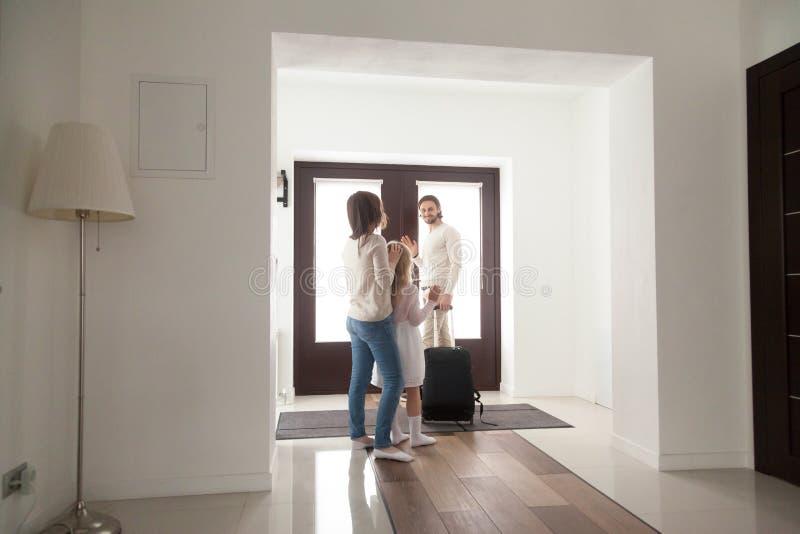 Familia en vestíbulo, padre que se va a casa con equipaje de la maleta fotos de archivo