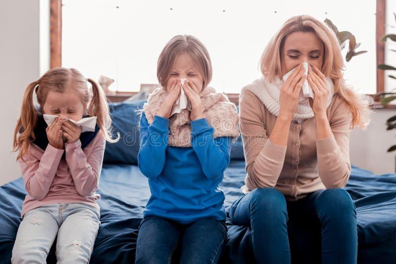 Familia enferma que se sienta en la cama foto de archivo libre de regalías