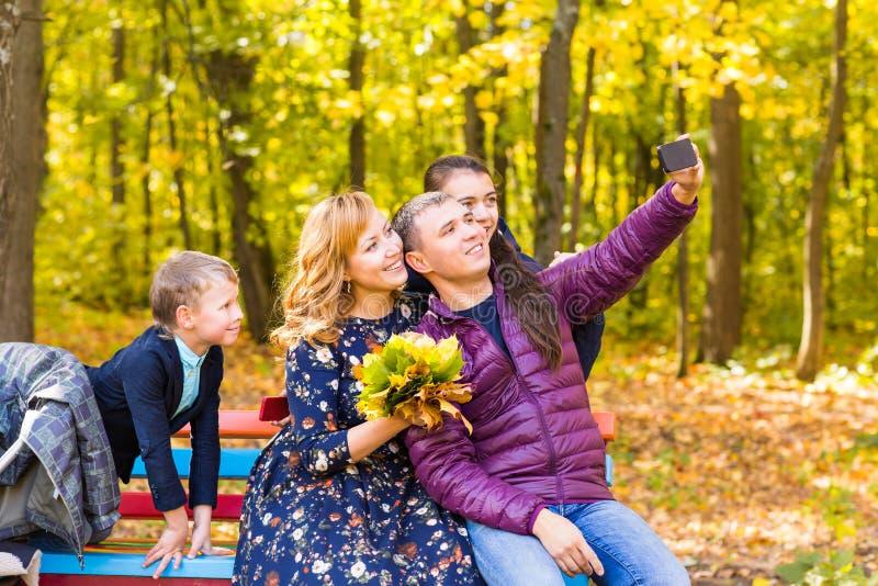 Familia, estación, tecnología y concepto de la gente - familia feliz que toma el selfie por smartphone en parque del autumnl fotos de archivo