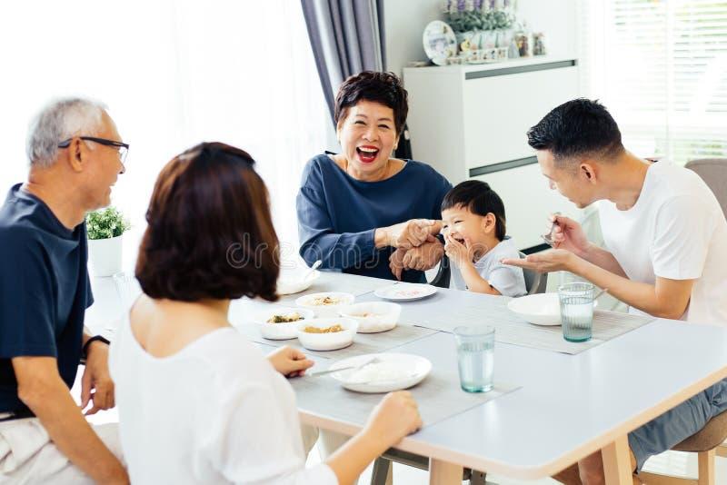 Familia extensa asiática feliz que cena en casa por completo de la risa y de la felicidad imagen de archivo