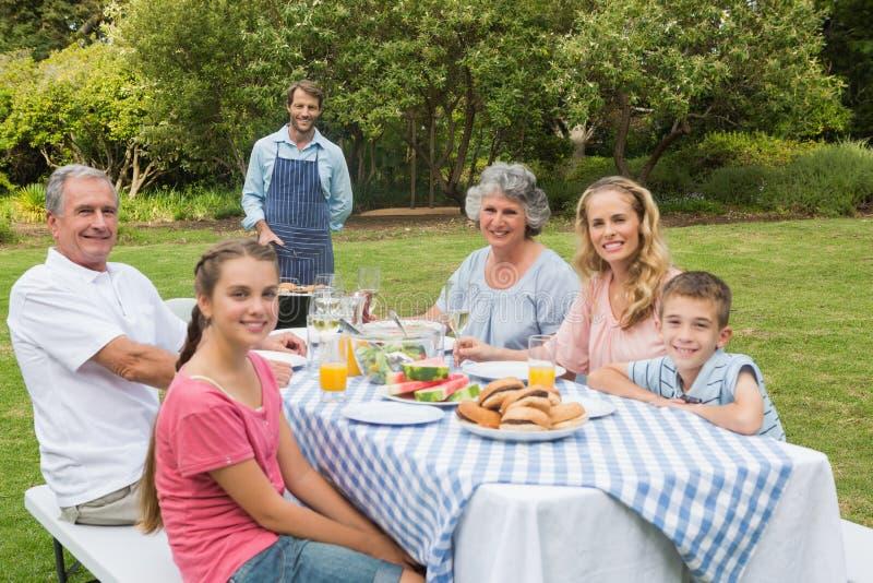Familia extensa feliz que tiene una barbacoa que es cocinada por el padre fotos de archivo libres de regalías