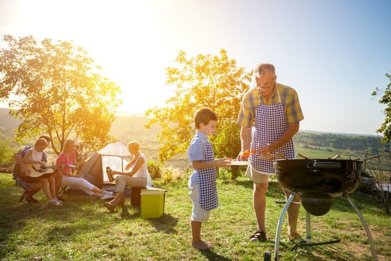 Familia extensa que cocina la barbacoa foto de archivo