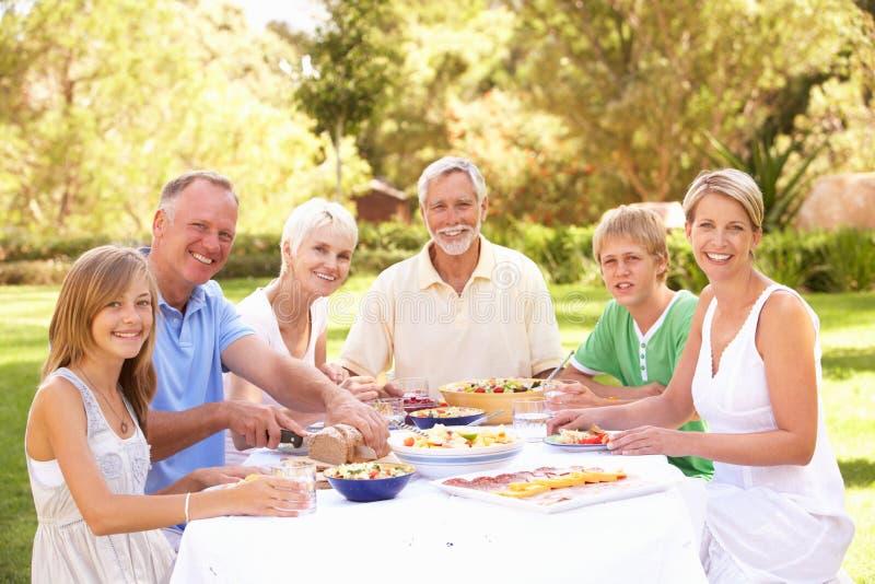 Familia extensa que disfruta de la comida en jardín foto de archivo libre de regalías