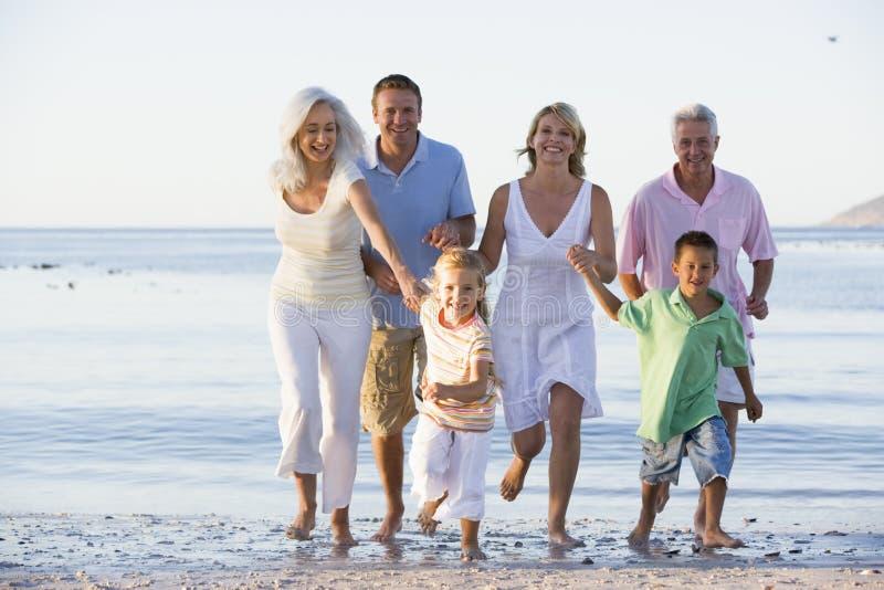 Familia extensa que recorre en la playa fotos de archivo