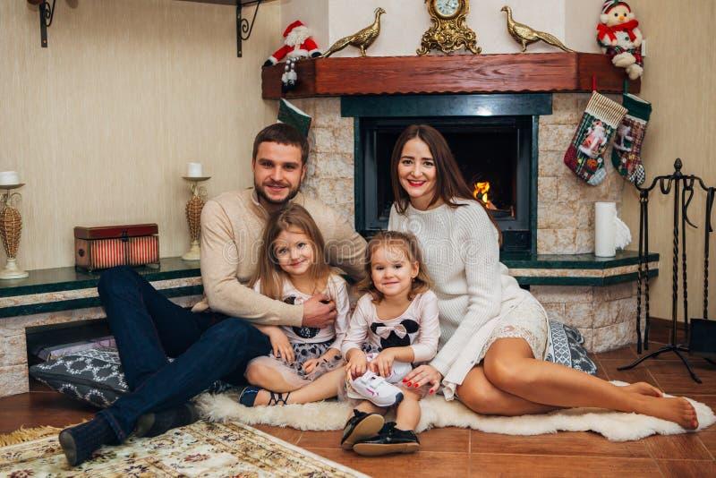 Familia extensa que se relaja junto en la chimenea foto de archivo libre de regalías