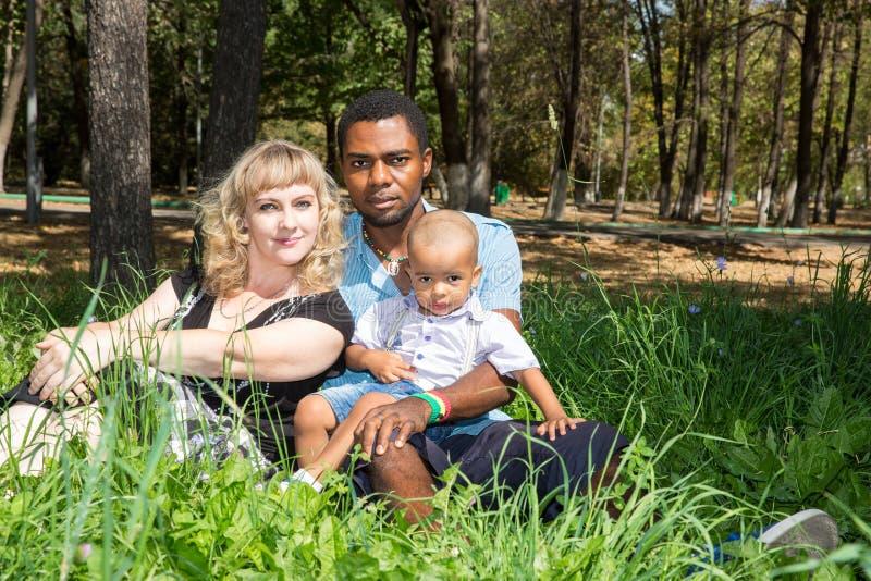 Familia feliz afroamericana: padre, mamá y bebé negros en la naturaleza imagen de archivo libre de regalías