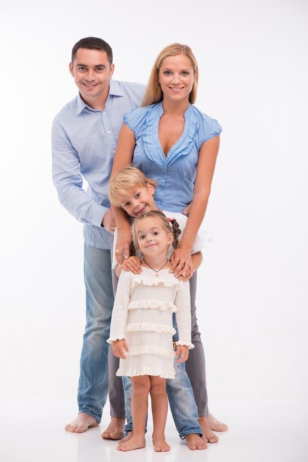 Familia feliz aislada en el fondo blanco fotos de archivo