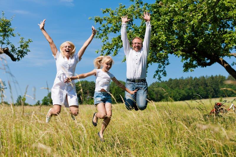 Familia feliz al aire libre que salta imagen de archivo libre de regalías