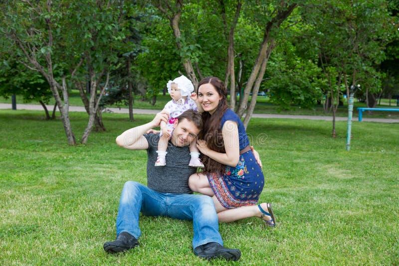 Familia feliz: bebé de la madre, del padre y de la hija en el parque foto de archivo