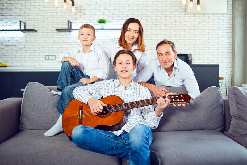 Familia feliz con canciones del canto de la guitarra en el cuarto foto de archivo