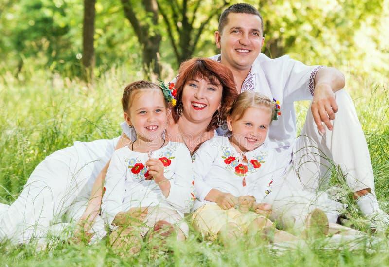 Familia feliz con dos hijas que se sientan en prado verde foto de archivo