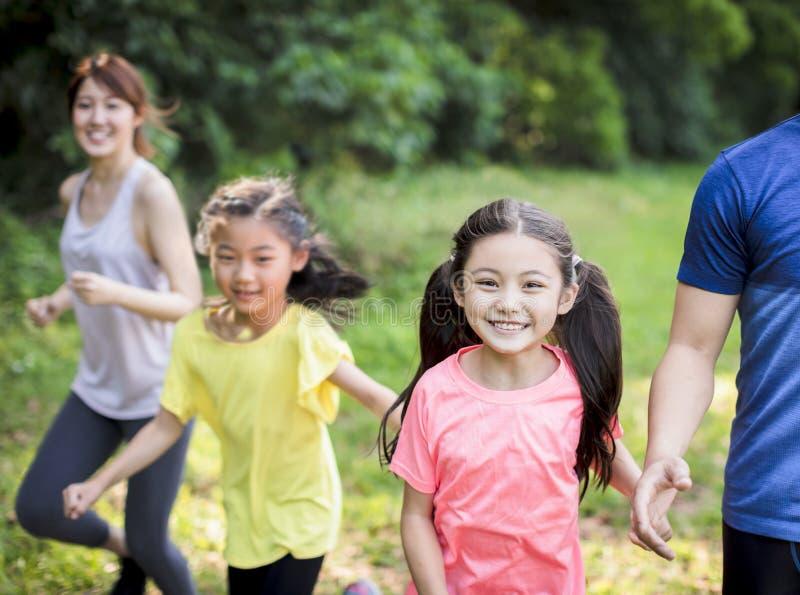 Familia feliz con dos niñas corriendo o trotando en el parque imagen de archivo libre de regalías