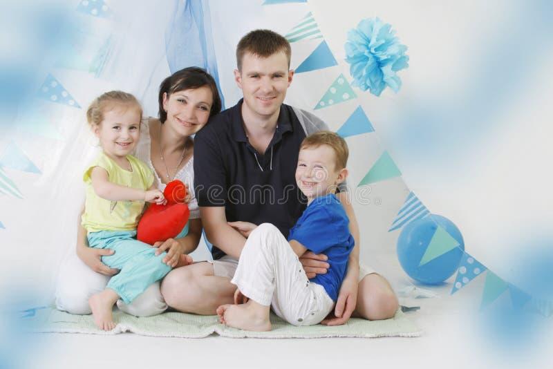 Familia feliz con dos niños en azul imagen de archivo