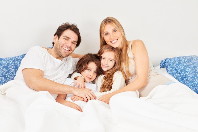Familia feliz con dos niños en cama fotografía de archivo libre de regalías