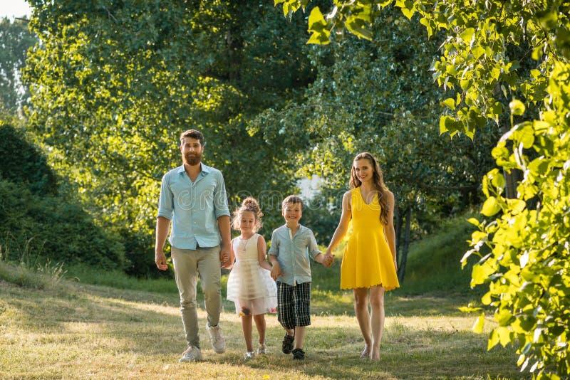 Familia feliz con dos niños que llevan a cabo las manos durante paseo recreativo fotos de archivo