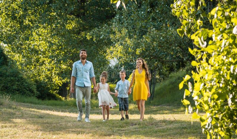 Familia feliz con dos niños que llevan a cabo las manos durante paseo recreativo foto de archivo libre de regalías