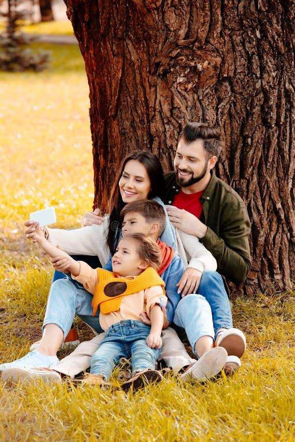 Familia feliz con dos niños que se sientan junto en hierba en parque y que toman un selfie imagen de archivo