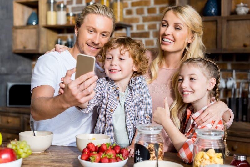 familia feliz con dos niños que toman el selfie mientras que desayunando imagen de archivo