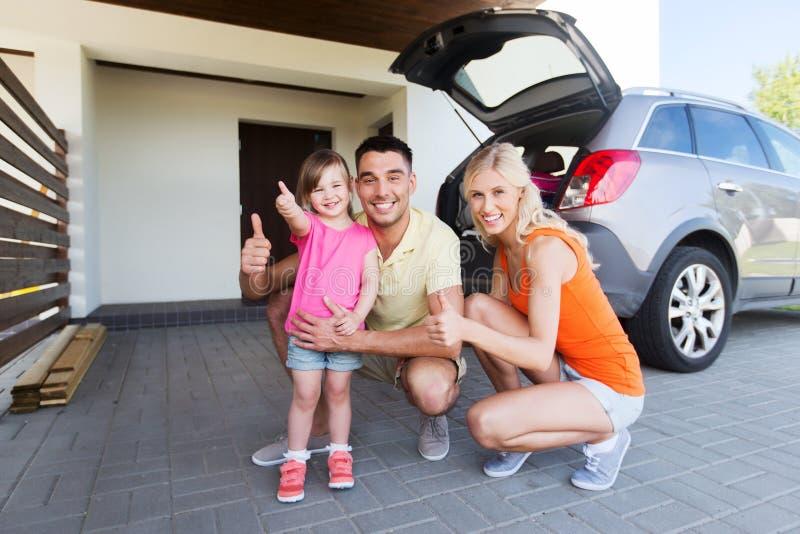 Familia feliz con el coche que muestra los pulgares para arriba en el estacionamiento imagenes de archivo