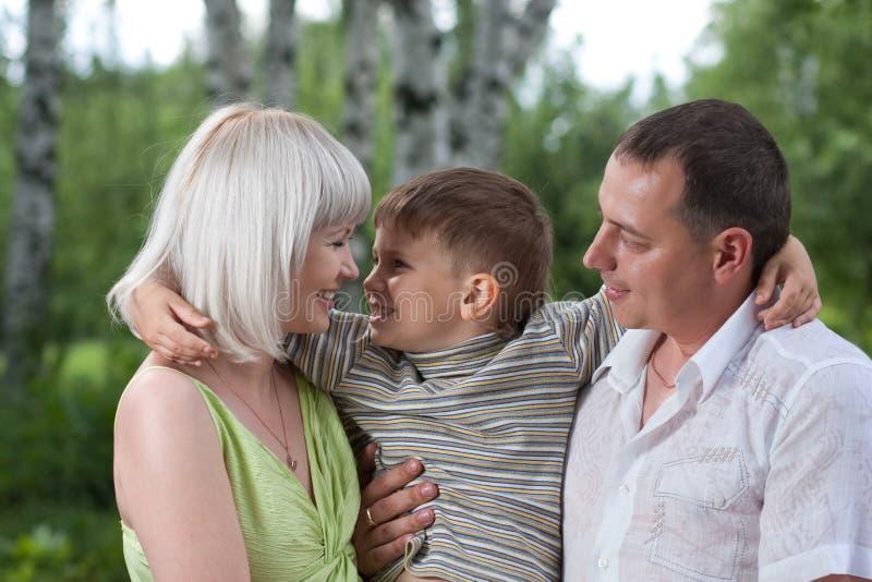 Familia feliz con el hijo en el parque fotografía de archivo libre de regalías